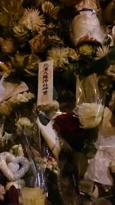 花束の上に日本の神社で入手したお札を置き、被害に遭われた方々のご冥福と合わせてこの国の平和を祈願