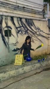 路上で繰り広げられていたアート・パフォーマンス。別途5HK$を支払うと、真っ黒なペンキ(?)に浸した菊の花を手渡され、建物の壁面に描かれた女性の周囲にこれを押し付けることで、作品づくりに参加することができる