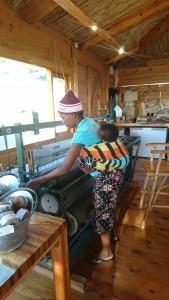 「ALPACA LOOM」のカフェ内でマフラーのようなものを織る女性の職人。機を織る彼女の存在そのものが1つの作品のように感じられる